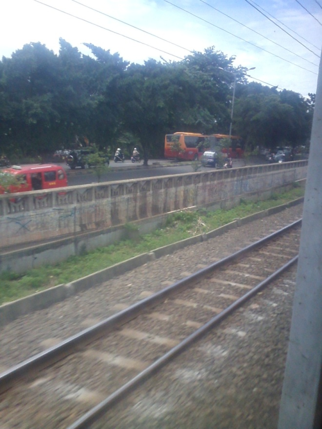 You can see the Busway (orange-red colored bus) over there, a famous public transport in Jakarta.. At this stage, the railways are side-by-side with I Gusti Ngurah Rai Street