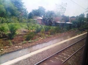 Jalan setapak dan parit besar di sisi kiri rel di daerah pemukiman warga Cilebut