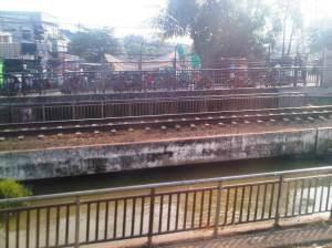 Salah satu kali kecil dan jalan perkotaan yang terlihat di sisi UTara rel tepat sebelum masuk St Bekasi